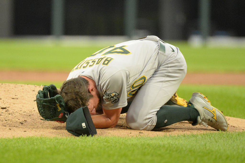 CHICAGO - AUGUST 17: Chris Bassitt #40 of the Oakland Athletics lies on the ground after being hit in the face by a line drive in the second inning off the bat of Brian Goodwin #18 of the Chicago White Sox on August 17, 2021 at Guaranteed Rate Field in Chicago, Illinois
