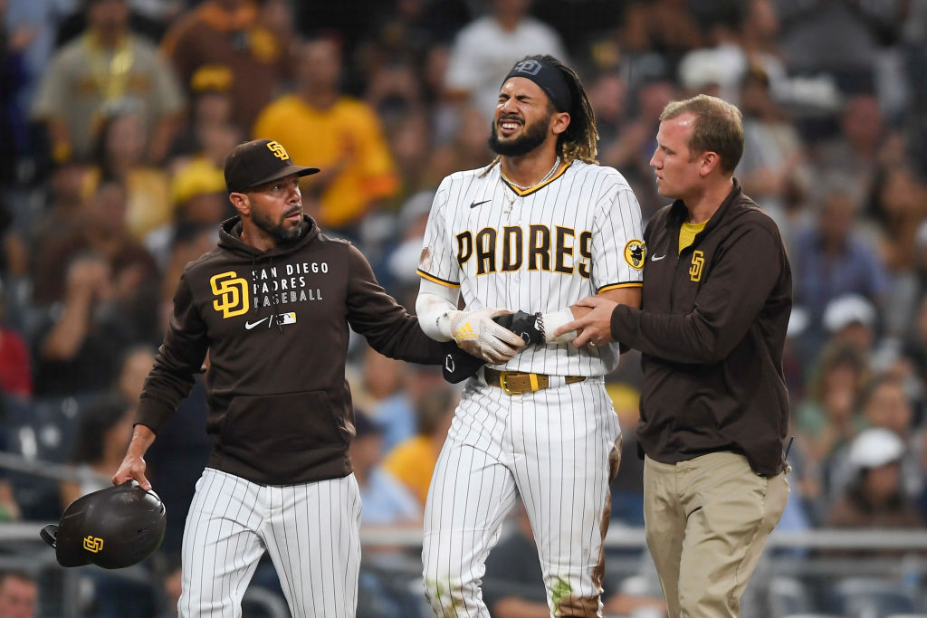 SAN DIEGO, CA - JULY 30: Fernando Tatis Jr. #23 of the San Diego Padres is helped off the field by manager Jayce Tingler and a trainer after he was injured during the first inning of a baseball game against the Colorado Rockies at Petco Park on July 30, 2021 in San Diego, California.